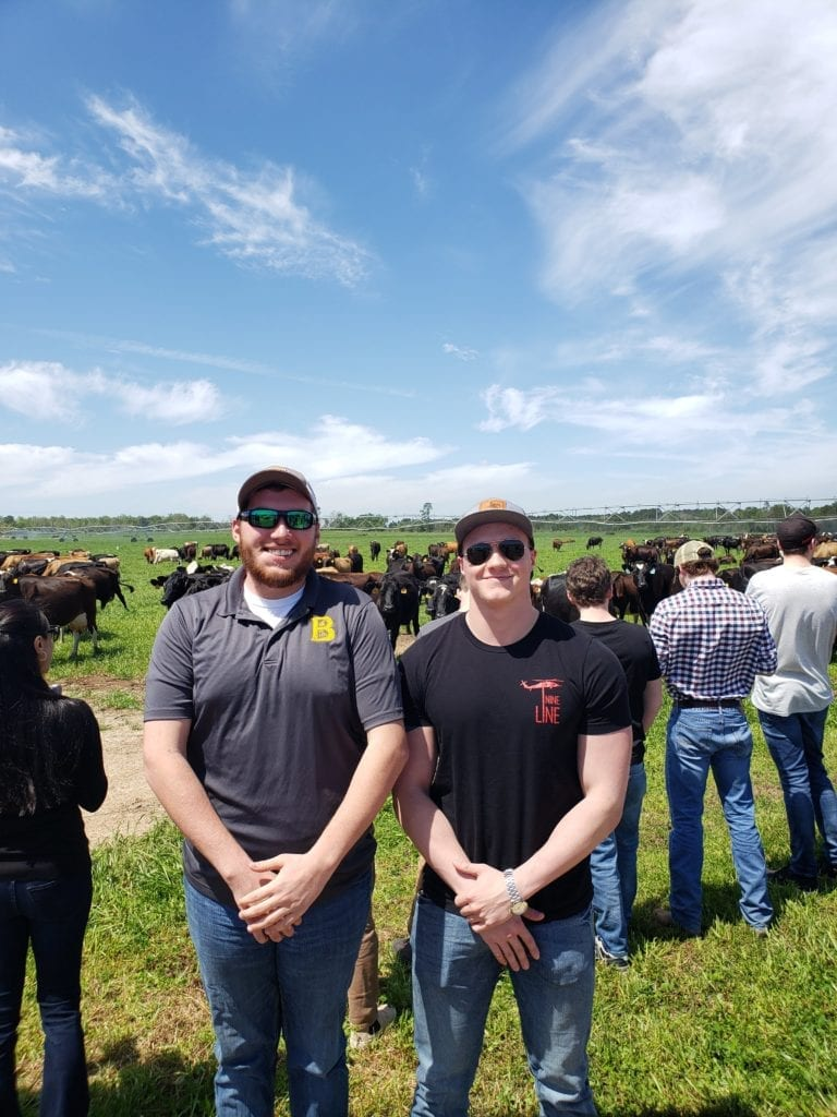 students smiling in front of cows