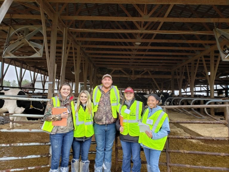 students posing in front of a barn